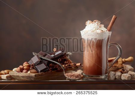 Hot Chocolate With Cream, Cinnamon, Chocolate Pieces And Various Spices On A Brown Background. Copy