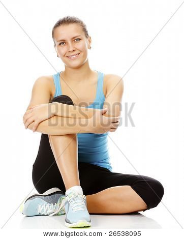 young brunette woman wearing sports clothes sitting on a white floor, isolated against white background