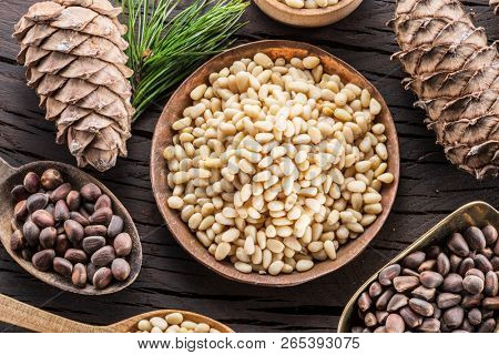 Pine nuts in the bowl and pine nut cones on the wooden table. Organic food. Top view.