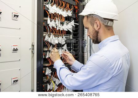 Technician Engineer Connects Optical Fibers Into Communication Switch In Data Center. Service Man In