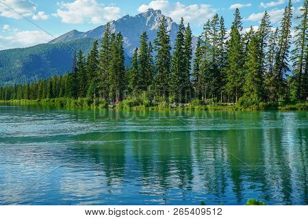 View Of Reflections Of Fur Trees On A Lake At Banff Indian Trading Post