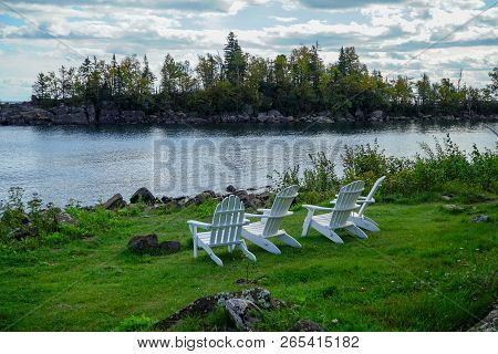Tranquil Scene With White Wooden Lawn Chairs On Green Grass Overlooking Lake Superior In Northern Mi