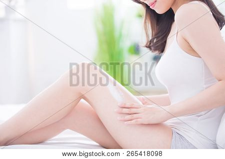 Woman Sitting On Bed And Applying Cream Onto Her Leg