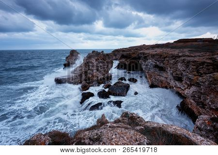Dramatic Nature Background - Big Waves And Dark Rock In Stormy Sea, Stormy Weather. Dramatic Scene.