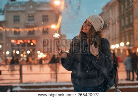 Beautiful Young Woman In Fur Coat Holding A Sparkler Enjoys Winter Christmas Mood In Old Snowy Europ