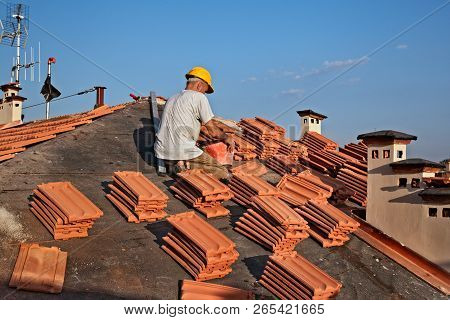 Construction Worker On A Roof Covering It With Tiles - Roof Renovation, Roofing Installation Of Tar