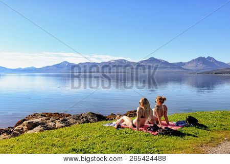 Tromso, Norway - August 18, 2016: Two Unidentified Girls Sunbathing In Tromso Southern Beach. Tromso