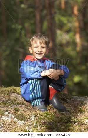 Kid Sitting On The Rock