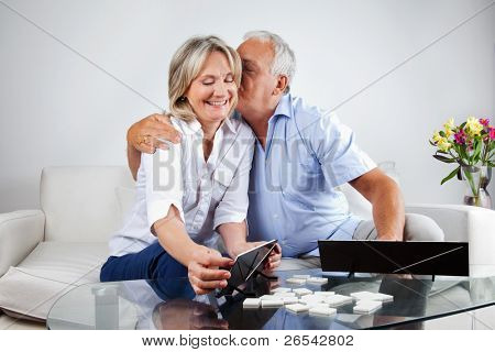 Loving husband kissing his wife while playing rummy at home.