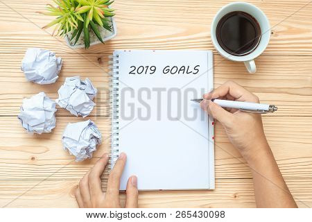 Businesswoman Writing 2019 Goals With Notebook, Crumbled Paper And Black Coffee Cup On Table. New Ye