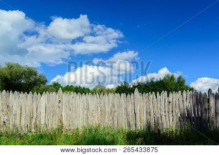 An Old Log Fence And A Blue Sky With Clouds. Security And Fencing. Protection Against Thieves.
