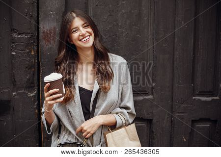 Gorgeous Young Woman With Cup Of Coffee And Bag Standing At Old Wooden Door In City Street. Stylish