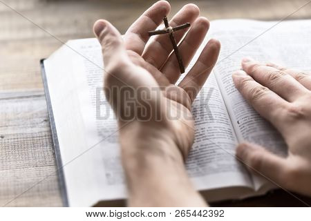 Wooden cross and bible in hand. The way to God through prayer. The hope of salvation. Life-giving light in the heart when reading the Holy Bible poster