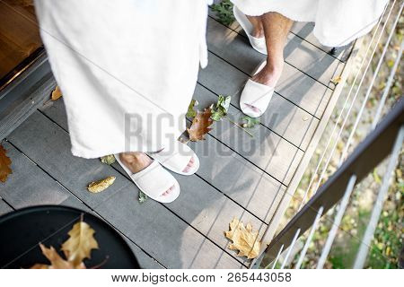 Couple In Bath Robe And Slipppers Standing On The Terrace With Beautiful Leaves Outdoors. View From