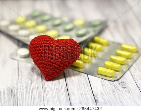 Medical Pills And Red Knitted Heart On Light Wooden Table, Selective Focus. Concept For Health Care,