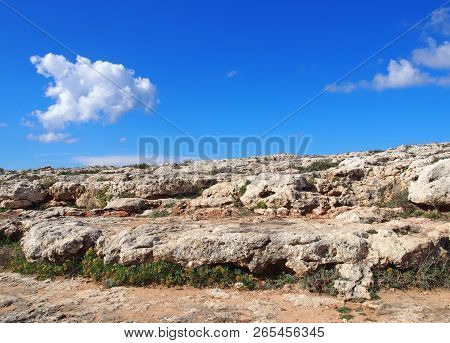 a rugged rocky arid limestone pavement landscape with vegetation in the cracks and blue sunlit sky with white clouds poster