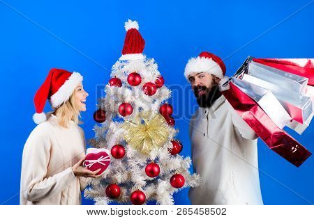 Christmas Shopping. Happy Family Couple In Sweaters&santa Hats Holds Gifts Or Presents. Christmas Pr