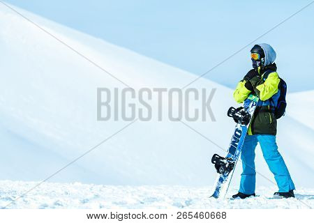 Winter Scenery. Full Length Shot Of A Snowboarder Wearing Snowboarding Sports Gear Posing With His S