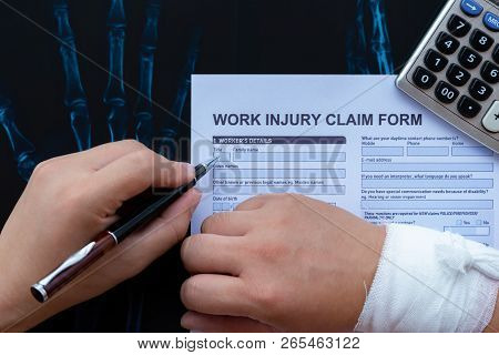 Filling Up A Work Injury Claim Form With A Wrapped Hand On Top Of An X-ray Film Medical And Insuranc