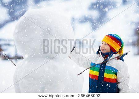 Kids Build Snowman. Children In Snow. Winter Fun.