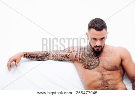 Nude Male Model Lies In White Bed. Muscular Tattooed Man Ready To St Valentines Day. Muscular Man Al