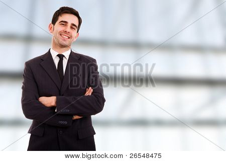 Closeup of a young smiling business man standing at a modern office