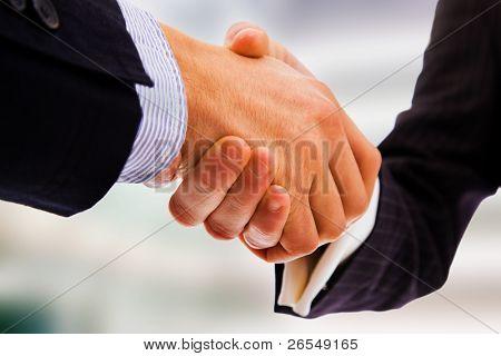 Business handshake between office bulding