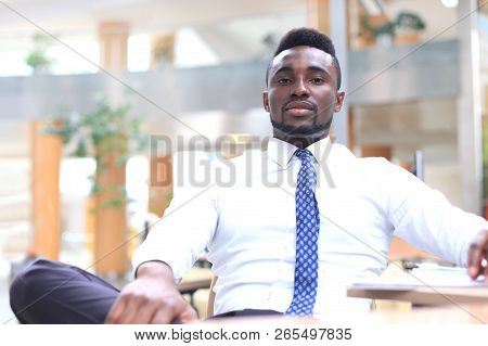 Happy Young African-american Businessman Looking At Camera At Workplace In Office.