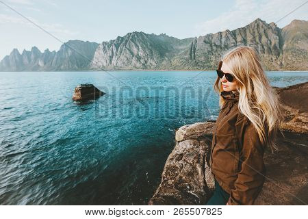 Young woman walking alone on beach cold sea traveling adventure lifestyle outdoor solitude emotions poster