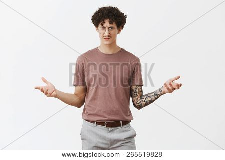 Bro What It Means. Confused Stunned And Displeased Jewish Guy With Curly Hair And Moustache In Glass