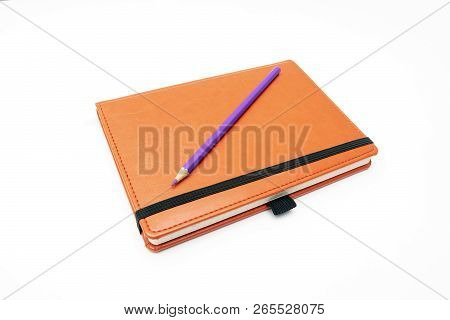 Orange Notebook With A Purple Pencil On A Notebook Surface Of A Notebook