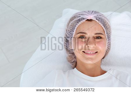 Woman after face biorevitalization procedure in salon. Cosmetic treatment poster