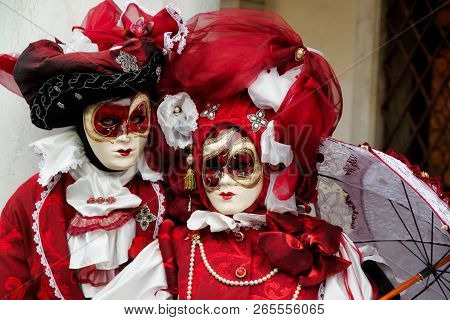 Carnival Pair Red-white Mask And Costume At The Traditional Festival In Venice, Italy