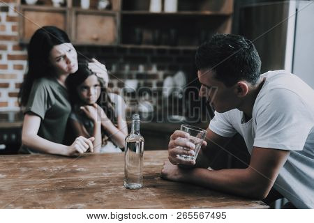 Wife And Kid Look At Father Getting Drunk At Home. Man Sits On Chair In Modern Kitchen Hold Glass Of