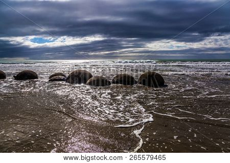 Boulders Moeraki - a group of large spherical boulders on the beach Koekokhe. Ocean evening tide. Travel to New Zealand. The concept of active, eco and photo tourism