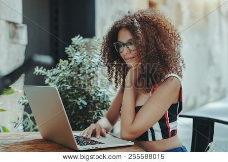 Portrait Of Pensive Beautiful Woman In Glasses Working With Her Laptop Outdoors; Charming Freelancer