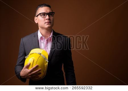 Young handsome multi-ethnic businessman with hardhat against bro poster