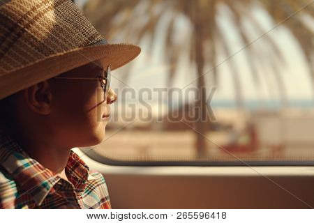 Cute Boy In Checkered Shirt Travelling By Train And Looking Into The Window While Passing Trough Sea
