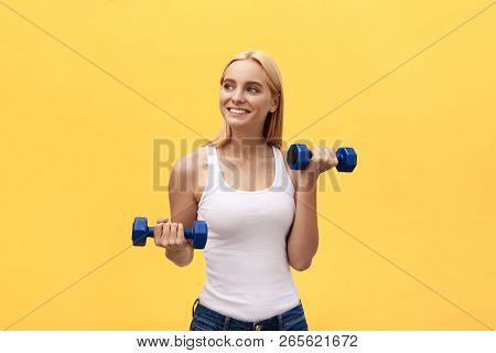 Fitness Woman Lifting Weights Smiling Happy Isolated On Yellow Background. Fit Sporty Caucasian Fema