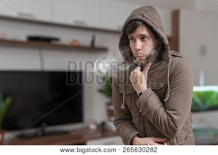 Young Man In Jacket Feel Cold At Home.