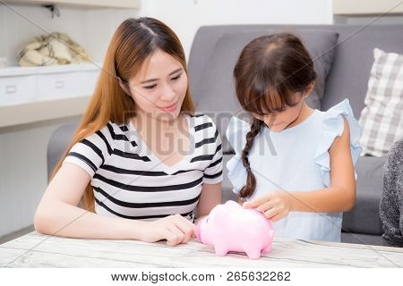 Asian Mother And Daughter Putting Coin In Piggy Bank, Mom And Kid With Deposit Account Family Togeth
