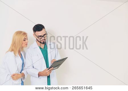 Doctors Looking And Discussing On Documents Paper.