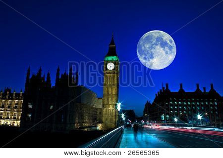 Night scene in London showing the Big Ben, a full moon and traffic on Westminster bridge