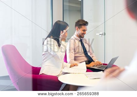 Real life small business  meeting with two attractive young adult business people or students have a discussion and looking at a laptop. This highlights modern technology and remote working