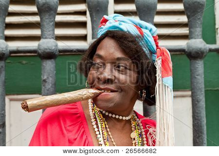 HAVANA-FEBRUARY 10:Wrinkled old lady with a huge cigar wears typical clothes and afrocuban religious necklaces February 10,2011 in Havana.