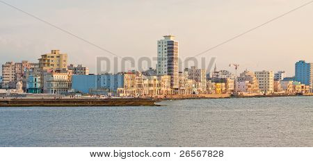 Panoramic view of the seashore of Havana with the famous promenade of El Malecon illuminated by the light of the sunset