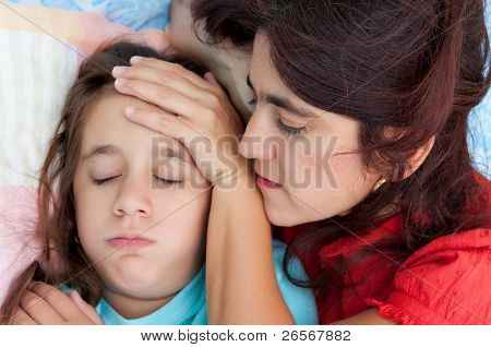 Latin mother checking the temperature of  her sick coughing daughter in bed