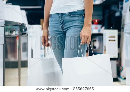 Cropped View Of A Young Woman With Shopping Paper Bags In A Home Appliance Store. Cyber Monday Conce