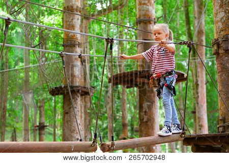 Brave Little Child In Safety Harness Climb On Tree Tops Route To Zip Line, Pass Hanging Bridge Obsta