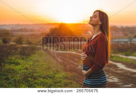 Beauty Romantic Is Pregnant Girl Outdoors Enjoying Nature Holding Her Belly. Beautiful Autumn Model